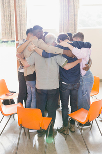 Men hugging in huddle in group therapyの写真素材 [FYI02854433]
