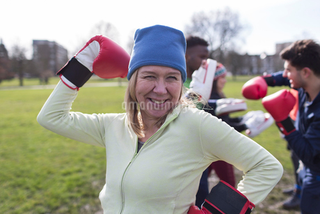 Portrait smiling, confident senior woman boxing in parkの写真素材 [FYI02854439]