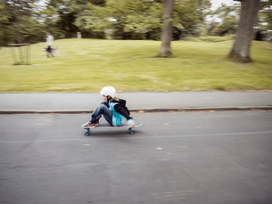 Sweden, Vastergotland, Gothenburg, Slottsskogen, Portrait of boy (10-11) riding longboard along roadの写真素材 [FYI02854457]