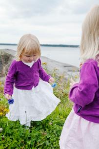 Sweden, Uppland, Roslagen, Twin girls (2-3) playing at seasideの写真素材 [FYI02854467]