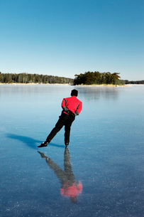 Sweden, Uppland, Loparo, Man ice-skating on frozen lakeの写真素材 [FYI02854485]