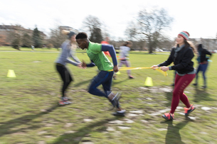 People racing, doing team building exercise in sunny parkの写真素材 [FYI02854598]