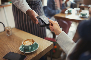 Customer with credit card paying worker with contactless payment in cafeの写真素材 [FYI02854616]