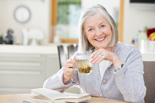 Older woman drinking tea and readingの写真素材 [FYI02854627]