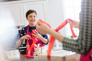 Smiling female caterers wrapping baked goods in boxes with red ribbon in kitchenの写真素材 [FYI02854628]