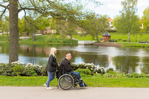 Sweden, Ostergotland, Mjolby, Man on wheelchair with personal assistant in parkの写真素材 [FYI02854635]