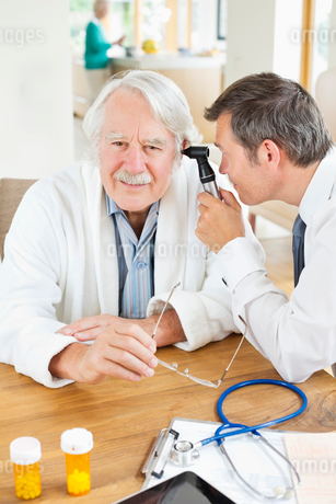 Doctor examining older man's ear at house callの写真素材 [FYI02854649]