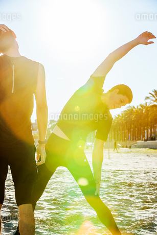 Male surfer stretching on sunny beachの写真素材 [FYI02854666]