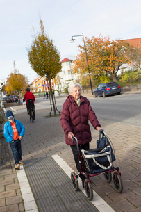 Sweden, Smaland, Tingsryd, Boy (6-7) walking with great-grandmotherの写真素材 [FYI02854678]