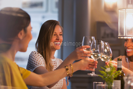 Smiling women friends toasting white wine glasses dining in restaurantの写真素材 [FYI02854709]