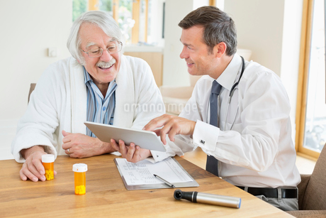 Doctor talking to older patient at house callの写真素材 [FYI02854714]