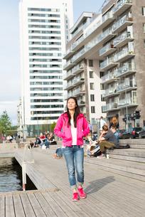 Sweden, Uppland, Stockholm, Kungsholmen, Hornsbergstrand, Woman in pink jacketの写真素材 [FYI02854722]