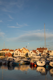 Sweden, West Coast, Bohuslan, Marstrand, Marina with sailboats on lake at sunsetの写真素材 [FYI02854773]