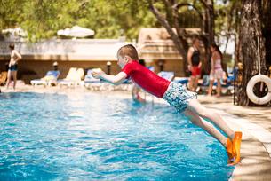 Turkey, Mugla, Marmaris, Boy (6-7) wearing diving slippers jumping into swimming pool at holiday resの写真素材 [FYI02854821]