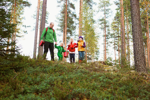Finland, Keski-Suomi, Jyvaskyla, Father with three daughters (2-5, 6-8) in pine tree forestの写真素材 [FYI02854911]