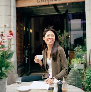 Sweden, Stockholm, Ostermalm, Smiling woman sitting at sidewalk cafeの写真素材 [FYI02854912]