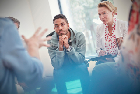 Attentive man and woman listening in group therapy sessionの写真素材 [FYI02854934]