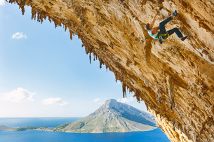 Greece, Dodecanese, Kalymnos, Rock climber on steep cliffの写真素材 [FYI02854955]