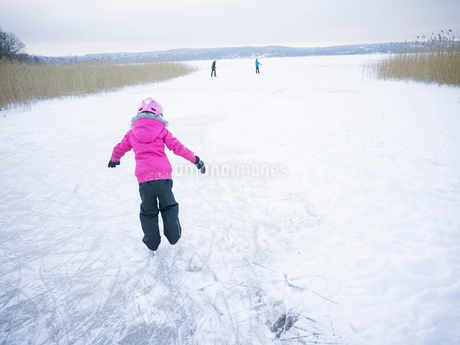 Sweden, Vastergotland, Lerum, Lake Aspen, Girl (6-7) ice-skating on surface of frozen lakeの写真素材 [FYI02854958]