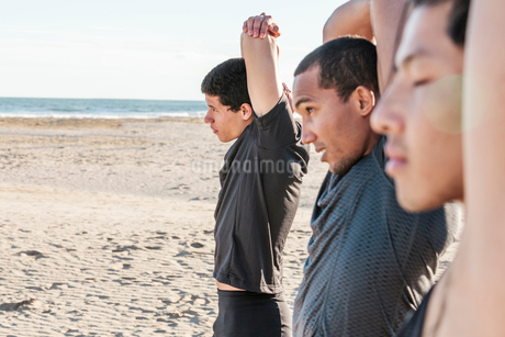 Male runners stretching arms on sunny beachの写真素材 [FYI02854985]