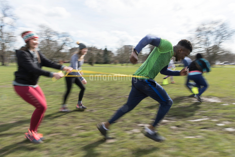 People racing, doing team building exercise in sunny parkの写真素材 [FYI02854995]