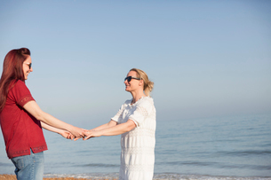 Affectionate lesbian couple holding hands on sunny ocean beachの写真素材 [FYI02855006]