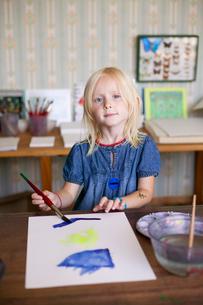 Sweden, Bohuslan, Skarhamn, Nordic Watercolor Museum, Portrait of girl (4-5) with paint brushの写真素材 [FYI02855014]