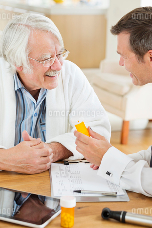 Doctor giving medication to older patient at house callの写真素材 [FYI02855023]