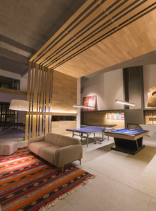 Illuminated modern, luxury home showcase interior game room with pool table and ping pong tableの写真素材 [FYI02855049]