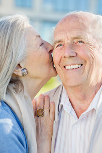Smiling older couple kissing outdoorsの写真素材 [FYI02855058]
