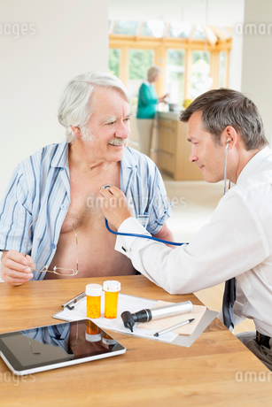 Doctor listening to older patient's heartbeat at house callの写真素材 [FYI02855120]