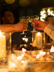 Friends toasting champagne glasses over table at candlelight Christmas dinnerの写真素材 [FYI02855139]