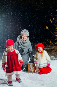 Finland, Portrait of grandmother with granddaughters (12-17 months, 2-3) in backyard at nightの写真素材 [FYI02855156]