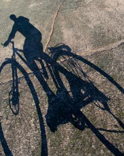 Finland, Turku archipleago, Shadow of man cyclingの写真素材 [FYI02855158]