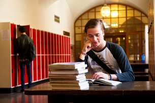 Sweden, Stockholm, Ostermalm, Male student reading at deskの写真素材 [FYI02855190]