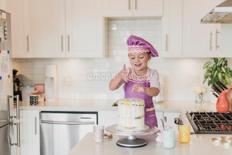 Smiling girl decorating cake in kitchenの写真素材 [FYI02855212]