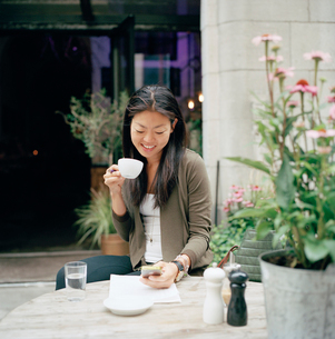 Sweden, Stockholm, Ostermalm, Smiling woman sitting at sidewalk cafe and text messagingの写真素材 [FYI02855248]