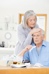 Older woman feeling sick husband's foreheadの写真素材 [FYI02855252]