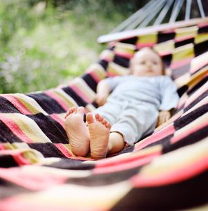Finland, Uusimaa, Lapinjarvi, Baby girl lying on hammock, focus on bare feetの写真素材 [FYI02855378]