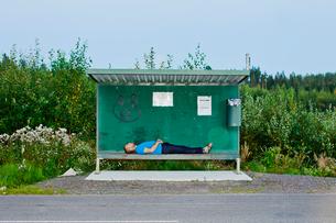 Finland, Jaala, Man sleeping at bus stopの写真素材 [FYI02855435]