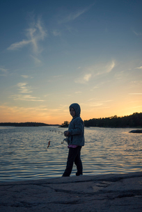 Sweden, Smaland, Tjust archipelago, Vastervik, Hasselo, Girl (4-5) fly fishing on lakeshore at sunseの写真素材 [FYI02855455]