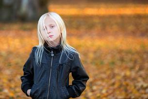 Sweden, Vastergotland, Lerum, Portrait of girl (8-9) wearing leather jacket with autumn leaves in baの写真素材 [FYI02855456]