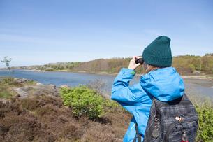 Sweden, Gothenburg Archipelago, Vastergotland, Styrso, Boy (10-11) with backpack photographing riverの写真素材 [FYI02855492]