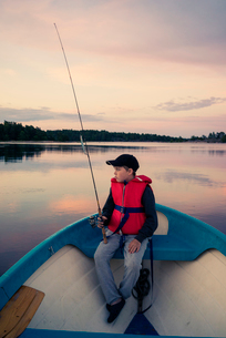 Sweden, Smaland, Tjust archipelago, Vastervik, Hasselo, Boy (10-11) fly fishing in boat on lakeの写真素材 [FYI02855516]