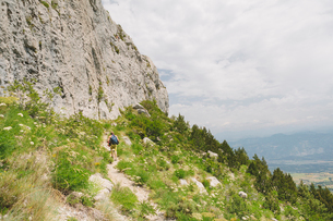 France, Pelleautier, Ceuse, Young man hiking along mountain footpathの写真素材 [FYI02855562]