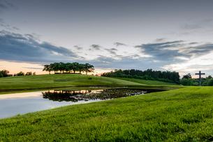Sweden, Sodermanland, Stockholm, Gamla Enskede, Skogskyrkogarden, Green landscape with pond at sunseの写真素材 [FYI02855570]