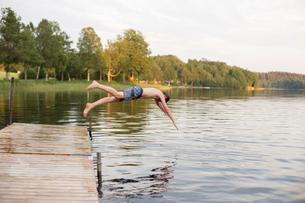 Sweden, Smaland, Braarpasjon, Boy (12-13) jumping into lake from jettyの写真素材 [FYI02855579]
