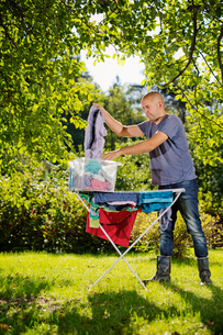 Finland, Paijat-Hame, Heinola, Man hanging laundry on drying rackの写真素材 [FYI02855603]