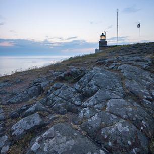 Sweden, Skane, Kullaberg, Rocks and lighthouse at duskの写真素材 [FYI02855607]