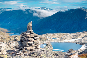 Norway, More og Romsdal, Sunnmore, Cairn of stones on top of Dalsnibba mountain, with lake seen beloの写真素材 [FYI02855608]